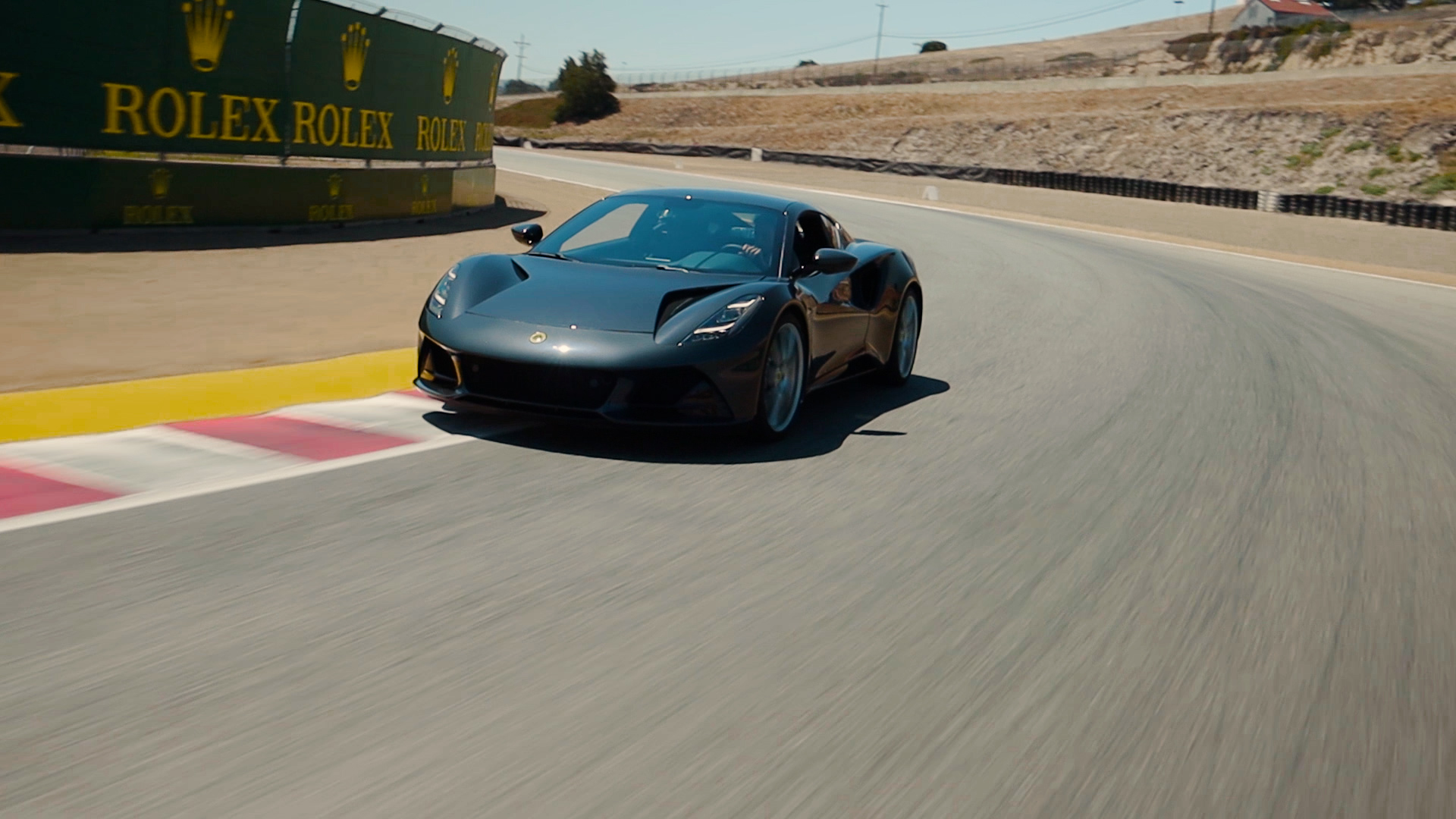 Lotus Emira Shadow Grey two door sports car in on the Laguna Seca race track driven by Jenson Button
